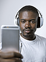 Young man with headphones looking at cell phone - STKF001429