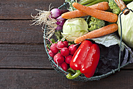 Wire basket with different vegetables on dark wood - CSF026167