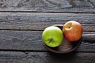 Two apples and wooden spoon on dark wood - CSF026149