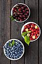 Three bowls of sour cherries, raspberries and blueberries on dark wood - CSF026133
