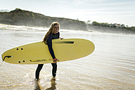 Spain, Colunga, young woman with surfboard on the beach - MGOF000436