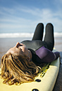 Spain, Colunga, young woman lying on surfboard sunbathing - MGOF000437