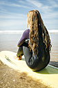 Spain, Colunga, back view of young woman sitting on surfboard on the beach - MGOF000440