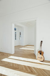 Guitar leaning on wall, empty room - CHAF001052