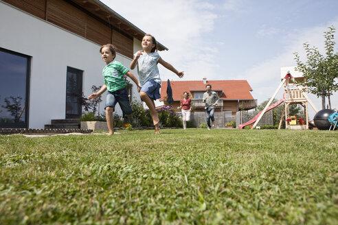 Carefree family running in garden - RBF003476