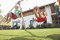 Brother and sister on a swing in garden - RBF003477