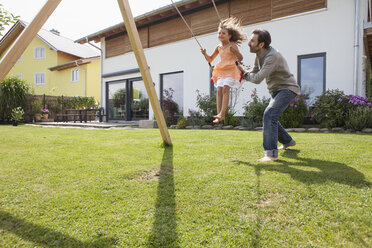 Father pushing daughter on a swing in garden - RBF003479