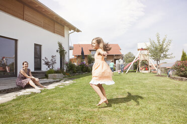 Playful girl with family in garden - RBF003486