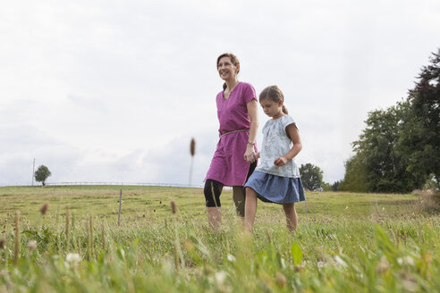 Mother walking with daughter on rural field - RBF003442