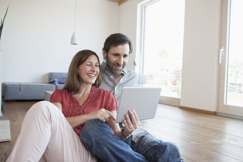 Mature couple sitting on floor, using digital tablet - RBF003289