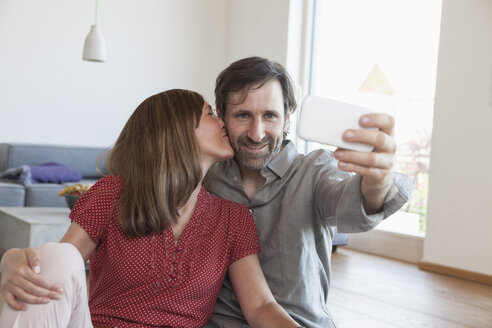 Mature couple sitting on floor taking selfie with smart phone - RBF003353