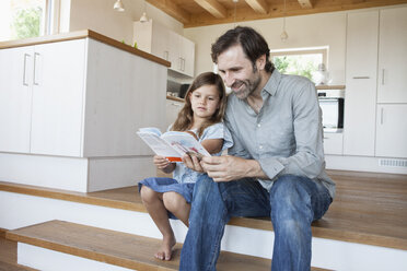 father and daughter sitting on kitchen steps readiing book - RBF003308