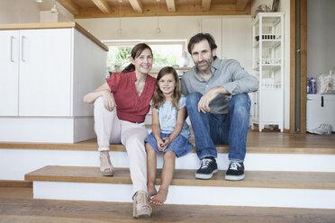 Happy family sitting on kitchen steps - RBF003362