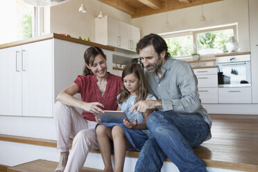 Happy family sitting on kitchen steps, daughter using digital tablet - RBF003309