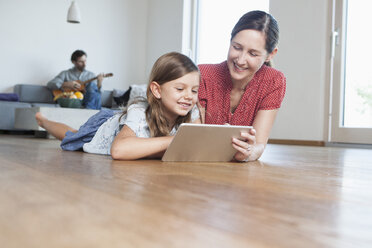 Mother and daughter lying on floor using digital tablet, father making music in background - RBF003312