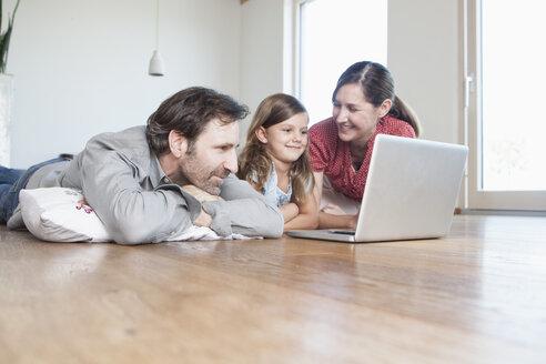 Happy family lying on floor, using laptop - RBF003314