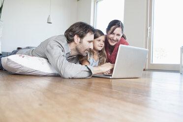Happy family lying on floor, using laptop - RBF003315