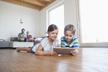 Brother an sister lying on floor using digital tablet, parents watching in background - RBF003319