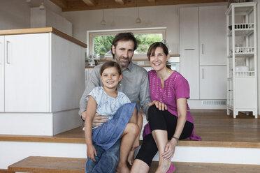 Happy family sitting on kitchen steps - RBF003326