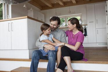 Happy family sitting on kitchen steps - RBF003327