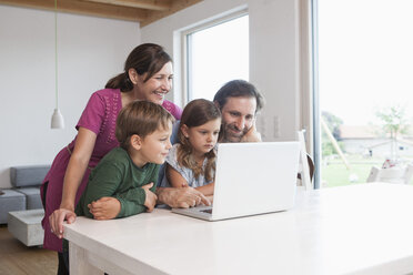 Happy family surfing the net together, using laptop - RBF003328