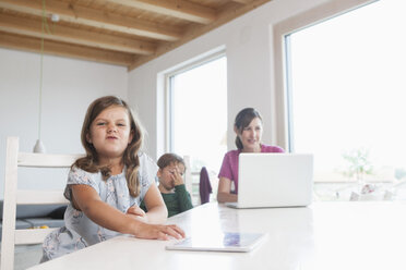 Little girl using digital tablet, mother and brother using laptop in background - RBF003330
