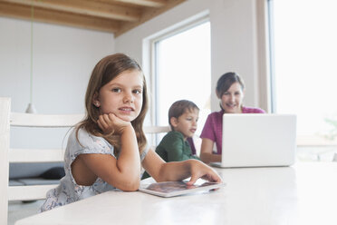 Little girl using digital tablet, mother and brother using laptop in background - RBF003331