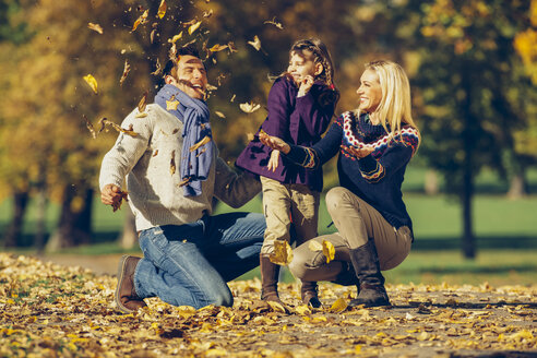 Parents and daughter playing with dry leaves in a park - CHAF001072