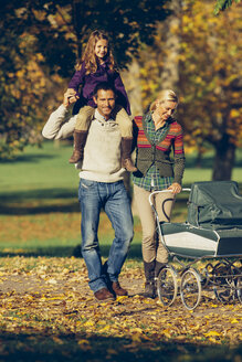 Family with baby carriage enjoying walk at the autumnal park - CHAF001076