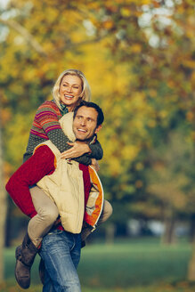 Man giving his girlfriend piggyback in the autumn park - CHAF001161