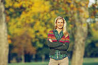 Portrait of smiling woman with crossed arms standing in autumnal park - CHAF001095