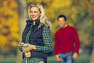 Portrait of smiling blond woman standing in autumnal park with a man in background - CHAF001082