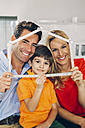 Family of three holding pocket rule in shape of a house - CHAF001101