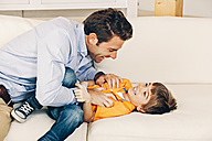Playful father and son on sofa - CHAF001115