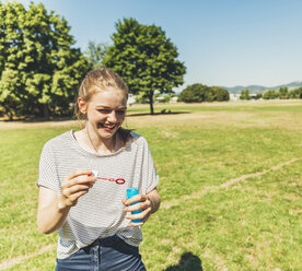 Happy teenage girl blowing soap bubbbles in park - AIF000081