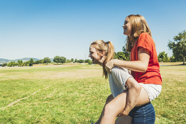Carefree teenage girl carrying friend piggyback in park - AIF000046