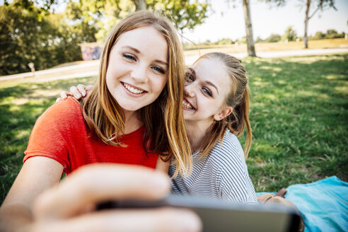 Two happy teenage girls taking a selfie on meadow - AIF000056