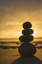 Spain, Valdovino, four stones in balance on the beach at backlight - RAEF000330