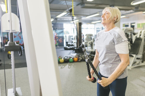 Smiling senior woman in gym exercising at cable machine - MADF000520