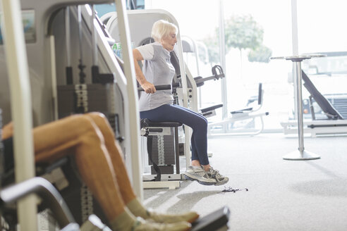 Senior woman in gym exercising at dip machine - MADF000523