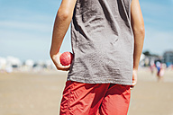 Back view of boy standing on the beach holding red boccia bowl in his hand - GEMF000316