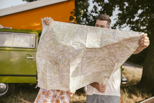 Couple looking at map in front of van in the nature - MF002054
