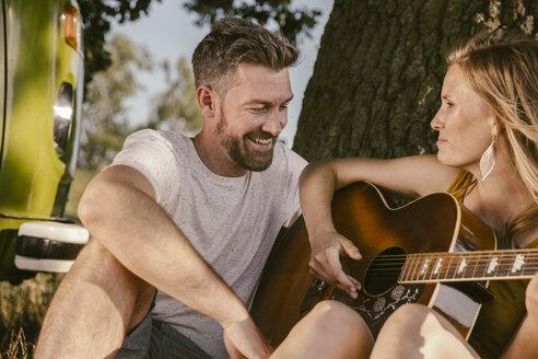 Couple making music at tree beside van - MFF002041