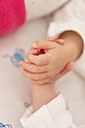 Newborn twins sleeping hand in hand, close-up - SHKF000347