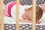 Newborn baby girl sleeping on cot - SHKF000352