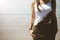 Woman standing at seafront wearing top and dungarees - GEMF000317