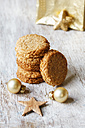 Stack of whole grain cocos cookies and Christmas decoration on wood - EVGF002077