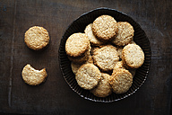 Bowl of whole grain cocos cookies  on dark wood - EVGF002088