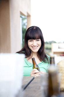 Happy young woman drinking a beer - TOYF001060