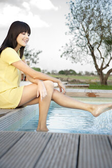 Happy young woman relaxing at swimming pool - TOYF001063